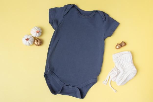 Vista superior de la maqueta de clobodysuit de bebé con calabazas sobre fondo amarillo para su texto o lugar de logotipo en la temporada de otoño