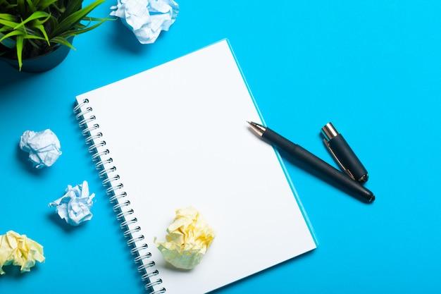 Vista superior maqueta del espacio de trabajo en azul con cuaderno, bolígrafo