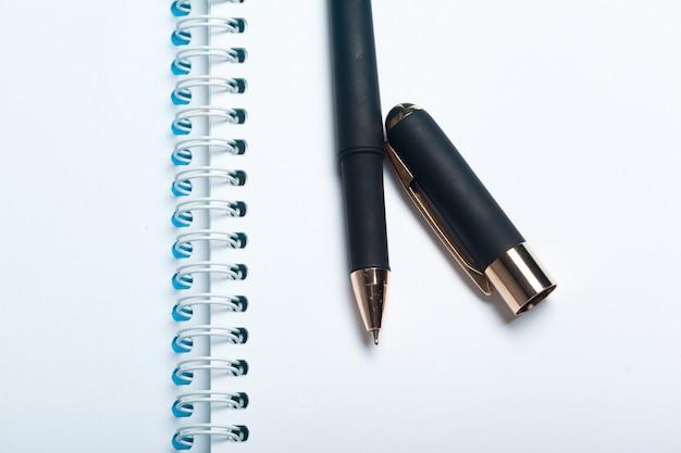 Vista superior maqueta del espacio de trabajo sobre fondo azul con cuaderno, bolígrafo