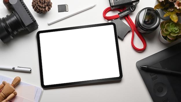 Vista superior de la maqueta de tableta digital, lápiz óptico y cámara en el espacio de trabajo del diseñador.