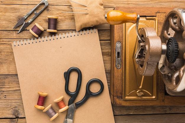 Vista superior de la máquina de coser vintage con cuaderno y tijeras