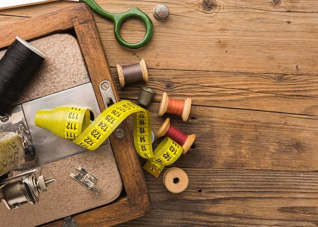 Vista superior de la máquina de coser vintage con hilo y cinta métrica