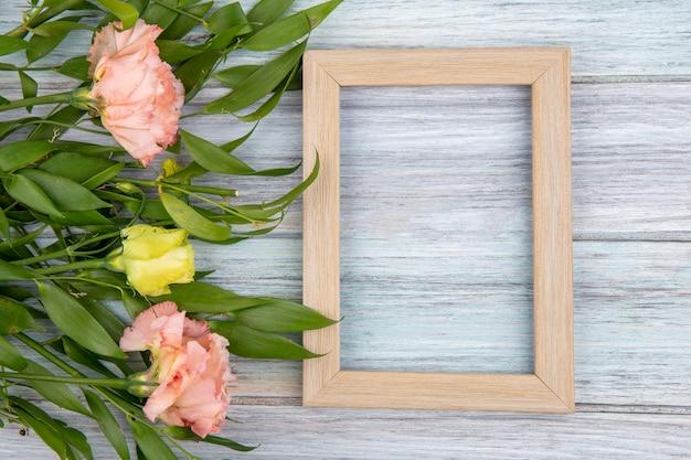 Vista superior de maravillosas flores con hojas y marco sobre superficie de madera gris