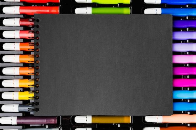 Vista superior de marcadores de colores y bloc de notas negro