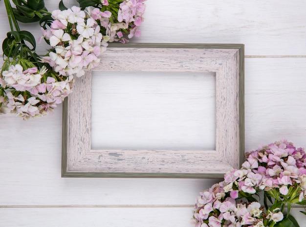 Vista superior del marco blanco con flores sobre una superficie blanca