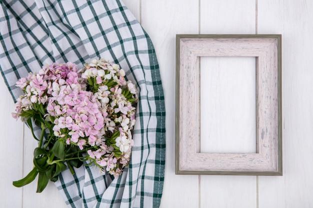 Vista superior del marco blanco con un ramo de flores sobre una toalla verde a cuadros sobre una superficie blanca