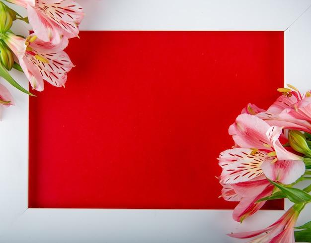 Vista superior de un marco blanco vacío con flores de color rosa alstroemeria y una postal sobre fondo rojo con espacio de copia