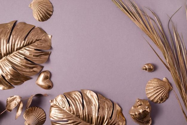 Vista superior del marco de la colección de hojas de monstera de oro, conchas marinas y corazones de oro.