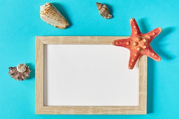 Vista superior del marco con conchas y estrellas de mar en azul. concepto de vacaciones de verano. sea flat lay