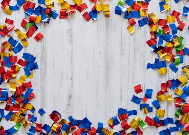 Vista superior del marco de confeti de colores sobre un fondo blanco de madera. temporada de vacaciones. celebracion.