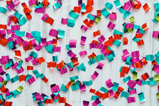 Vista superior del marco de confeti de colores sobre un fondo blanco de madera.