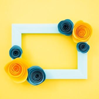 Vista superior marco floral azul sobre fondo amarillo