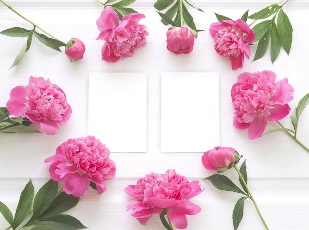 Vista superior del marco de flores de peonía con papel blanco claro