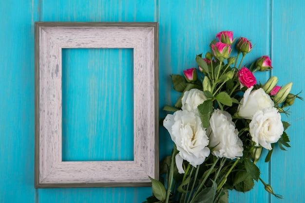 Vista superior del marco y flores sobre fondo azul con espacio de copia
