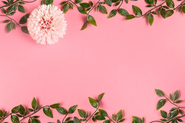 Vista superior del marco de follaje en papel con flor