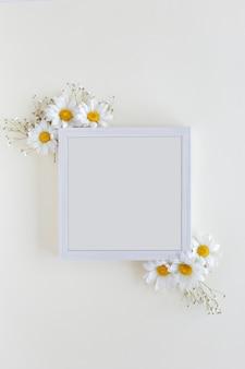 Vista superior del marco de fotos en blanco decorado con flores de margarita blanca sobre fondo blanco