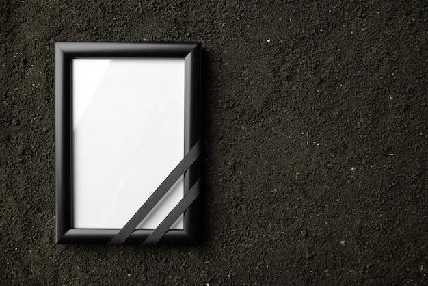 Vista superior del marco de fotos en el suelo oscuro