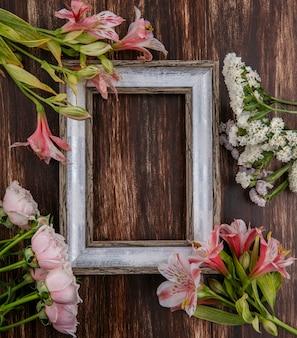 Vista superior del marco gris con flores alrededor de los bordes sobre una superficie de madera