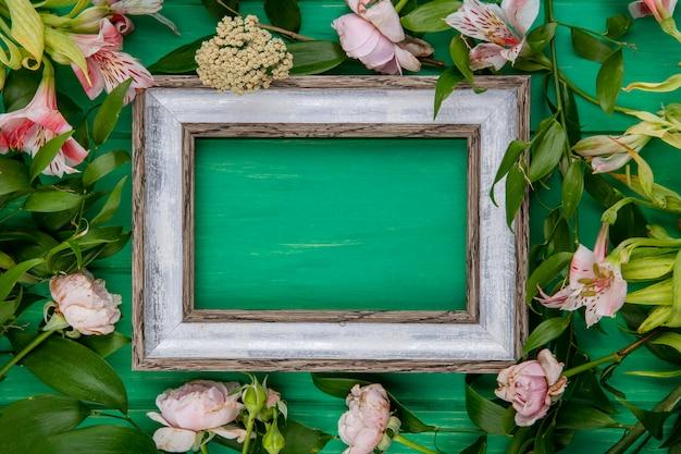 Vista superior del marco gris con flores de color rosa claro y ramas de hojas sobre una superficie verde