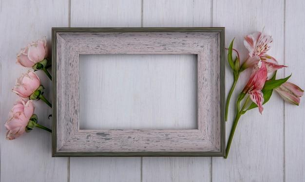 Vista superior del marco gris con rosas de color rosa claro y lirios sobre una superficie gris