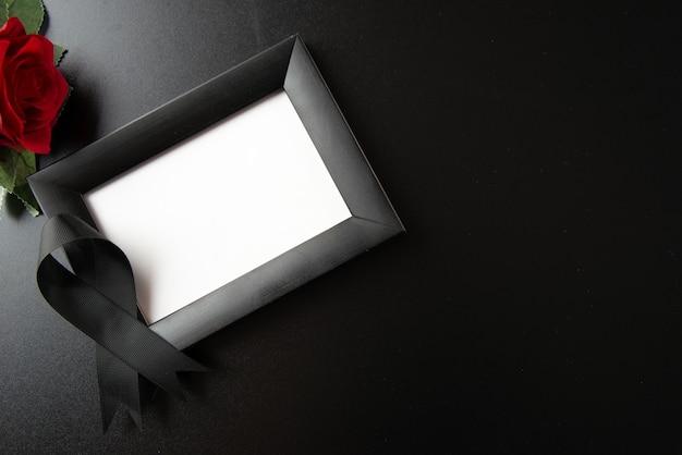 Vista superior del marco de imagen con lazo negro en la pared oscura