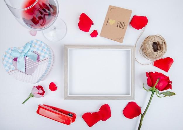 Vista superior de un marco de imagen vacío con una caja de regalo vaso de vino bola de cuerda rosas de color rojo pequeña grapadora postal sobre fondo blanco