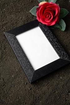 Vista superior del marco de imagen vacío con flor roja en suelo oscuro