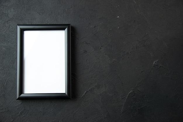 Vista superior del marco de imagen vacío en la pared oscura