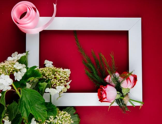 Vista superior de un marco de imagen vacío con rosas rojas con hinojo y viburnum en flor sobre fondo rojo.