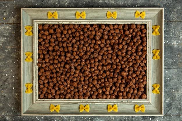 Vista superior de un marco de madera con pasta farfalle y relleno de bolas de maíz con cereales de chocolate