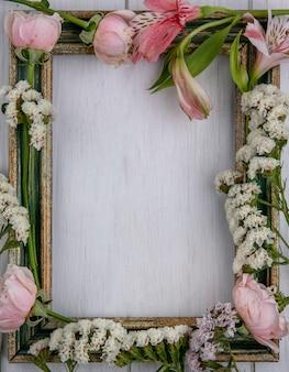 Vista superior del marco de oro verdoso con flores de color rosa claro sobre una superficie gris