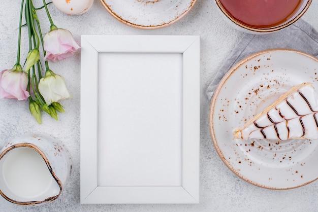 Vista superior del marco con pastel y rosas