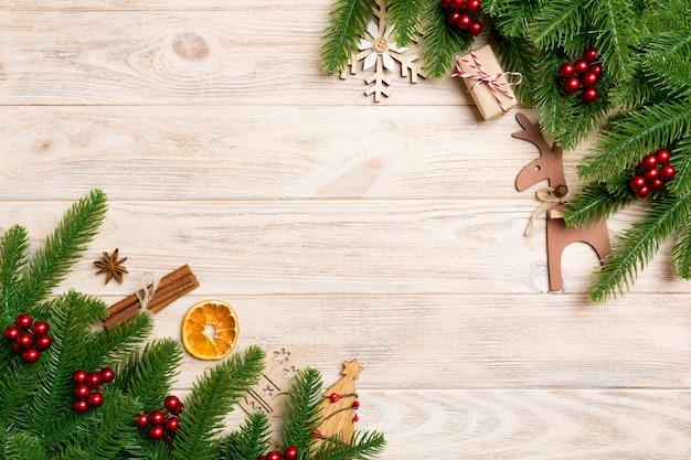 Vista superior del marco de ramas de abeto y decoraciones navideñas en madera.
