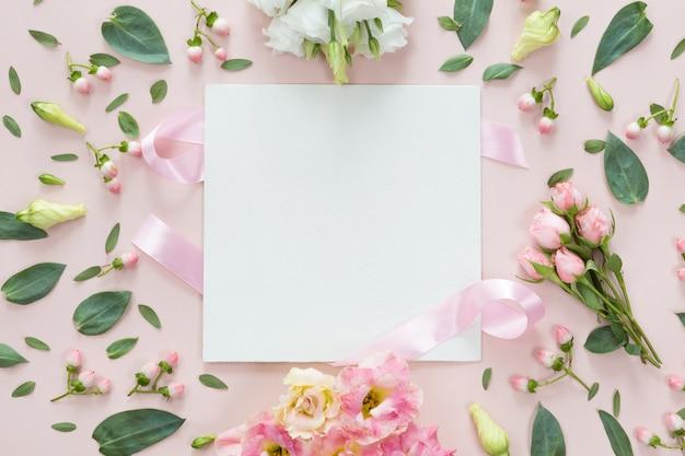 Vista superior del marco redondo de flores con hojas y copia espacio aislado sobre fondo rosa, plano lay. concepto de tarjeta de felicitación