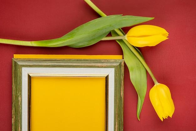 Vista superior de un marco vacío y tulipanes de color amarillo en la mesa roja