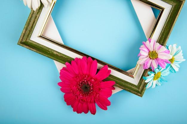 Vista superior de marcos vacíos con coloridas flores de gerbera con margaritas sobre fondo azul.