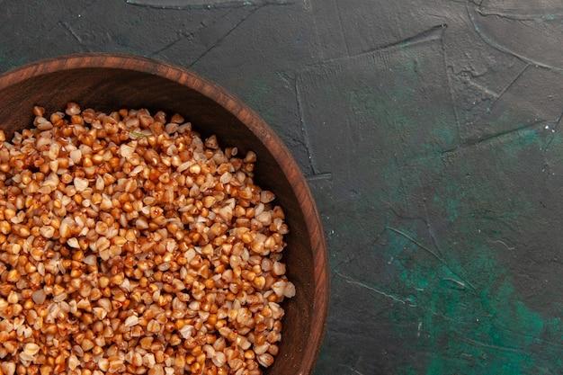 Vista superior más cercana comida sabrosa de trigo sarraceno cocido dentro de la placa marrón sobre la superficie de color verde oscuro
