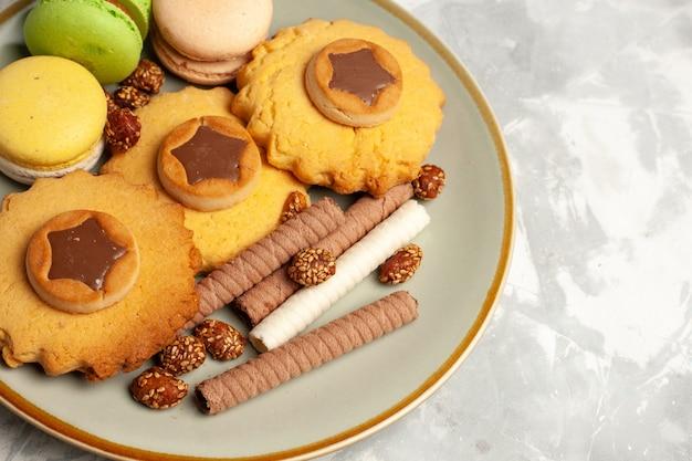 Vista superior más cercana macarons franceses con pasteles y galletas en la superficie blanca clara