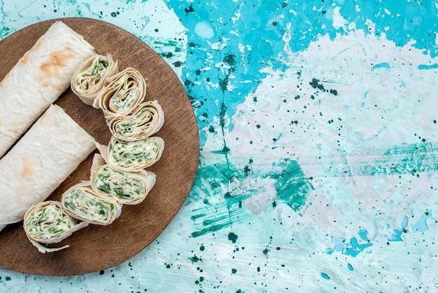 Vista superior más cercana de sabrosos rollos de verduras enteras y en rodajas con verduras en azul