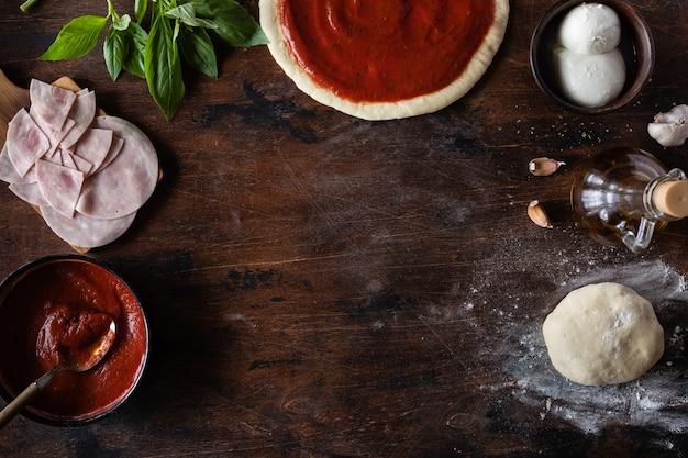 Vista superior de masa cruda, ingredientes y especias.