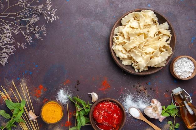 Vista superior de masa cruda en rodajas con condimentos sobre fondo oscuro, pasta, pasta, comida, cena, comida