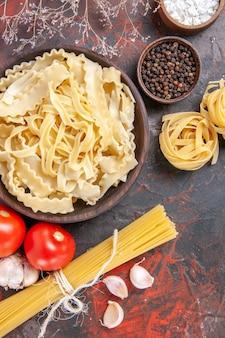 Vista superior de masa cruda en rodajas con condimentos en la superficie oscura de la masa de pasta comida oscura