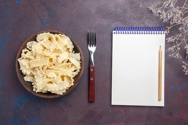 Vista superior de la masa cruda en rodajas dentro de la placa marrón sobre el fondo oscuro, comida, cena, pasta, masa