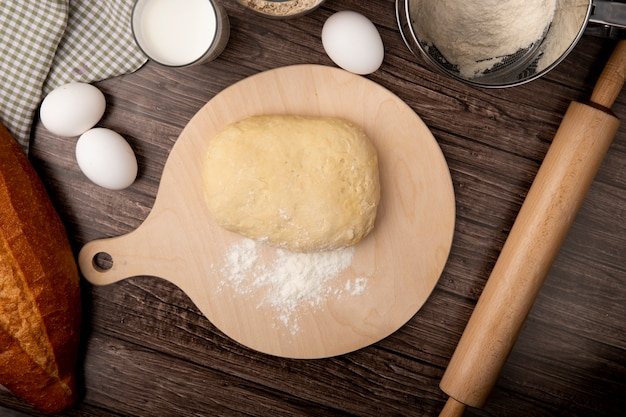 Vista superior de la masa y la harina en la tabla de cortar con huevos leche rodillo sobre fondo de madera