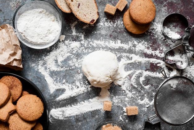 Vista superior de la masa en el mostrador con harina y galletas