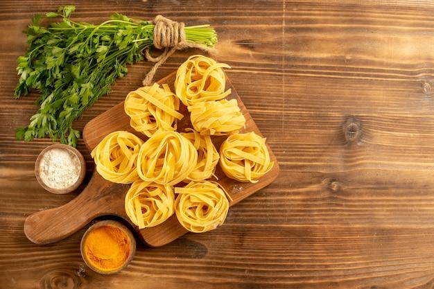 Vista superior de la masa de pasta cruda con condimentos y verduras en el fondo marrón, pasta, comida, comida, pasta