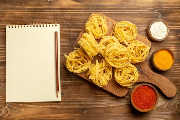 Vista superior de la masa de pasta cruda con diferentes condimentos en la pasta de comida de comida de masa de fondo marrón