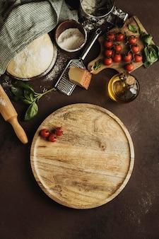Vista superior de la masa de pizza con tablero de madera y tomates