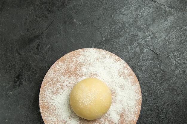 Vista superior de masa redonda cruda con harina sobre fondo gris oscuro masa harina harina alimentos crudos
