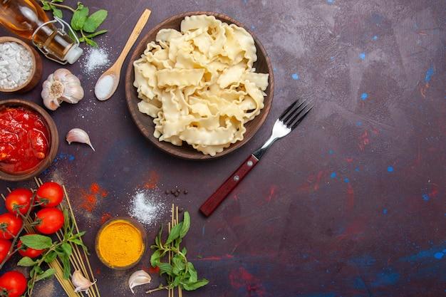 Vista superior de masa en rodajas con salsa de tomate y tomates en el fondo oscuro cena de pasta de comida de masa de comida